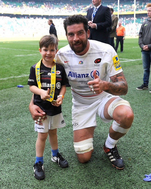 Jim Hamilton of Saracens celebrates with his son after winning the Aviva Premiership Rugby Final between Bath Rugby and Saracens at Twickenham Stadium on Saturday 30th May 2015 (Photo by Rob Munro)