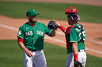 Boston Red Sox pitcher Kevin McCarthy (61) and catcher Kevin Plawecki (25) celebrate closing out a Major League Spring Training game against the Minnesota Twins on March 17, 2021 at JetBlue Park in Fort Myers, Florida.  (Mike Janes/Four Seam Images)