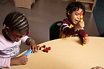 Education preschool 4 year olds girl and boy sorting colored plastic cubes into a pattern by color