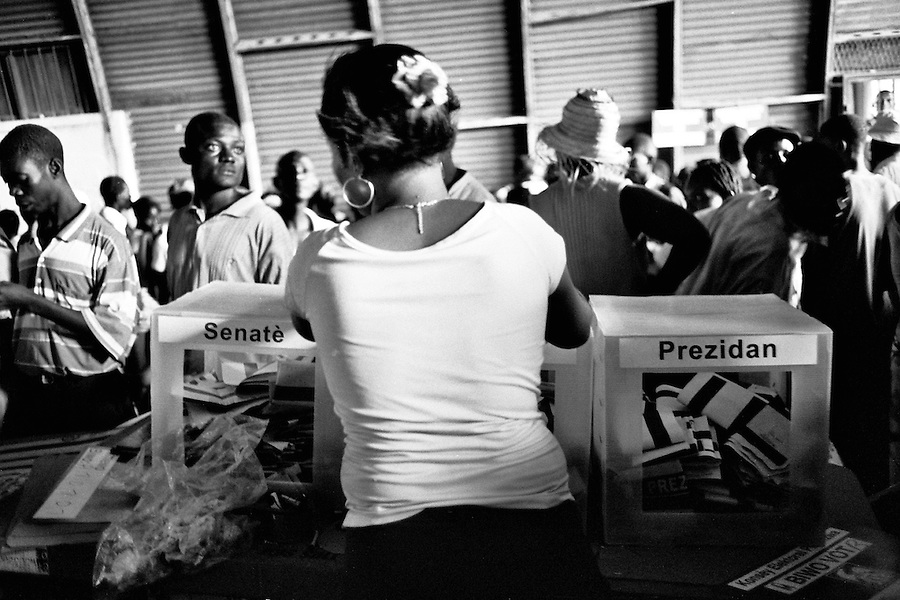 Haitian woman placing the sheets of paper containing the chosen candidates inside of the ballot boxes at closet voting station to Cite Soleil on the day of the elections.