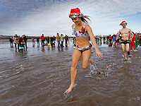 Pictured: A young woman with a Santa hat take to the sea. Wednesday 25 December 2019<br /> Re: Hundreds of people in fancy dress, have taken part in this year's Porthcawl Christmas Swim in south Wales, UK.