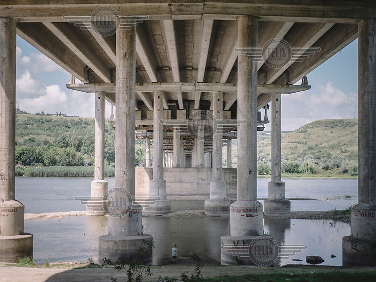 A boy fishing beneath a bridge that unites both banks of Dniester River.