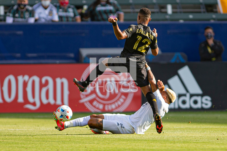 CARSON, CA - MAY 8: Julian Araujo #22 of the Los Angeles Galaxy slide tackles Diego Palacios #12 of LAFC during a game between Los Angeles FC and Los Angeles Galaxy at Dignity Health Sports Park on May 8, 2021 in Carson, California.