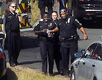 Police officers come to the comfort of a shaken officer, holding the bottle,  moments after a suspect was shot after a bank robbery and chase, Friday, August 14, 2015, in Bolton. The chase started after a bank robbery on Buckland Road in South Windsor. The chase went through surface roads in Manchester ending in Bolton Notch with a confrontation and the suspect being shot. Among those in the photo are  Manchester Police Chief Marc Montminy, left, and long time Manchester Police Officer Bernie Hallums, right.  (Jim Michaud / Journal Inquirer)