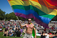 Man waving rainbow colored flag, Seattle PrideFest 2016, Pride Festival, Washington, USA.
