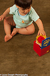 10 month old baby boy siting leaning forward to touch cloth jack in the box toy