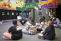 """Artist Ibi Olufemi Alao (left) reads to Elmwood Middle School students from his book """"Ibi's Fireflies"""", Friday, April 30, 2021 at the Rogers Experimental House in Rogers. About 30 eighth-grade art students from Elmwood Middle School went on an art tour through downtown Rogers at the Anime Cafe, White's Jewelry and the Rogers Experimental House where they met resident artist Ibi Olufemi Alao. Check out nwaonline.com/210501Daily/ for today's photo gallery. <br /> (NWA Democrat-Gazette/Charlie Kaijo)"""