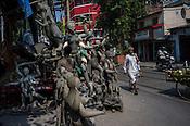 A hindu priest walks past a sculptor painting the sculptors of Hindu Goddess (Kali) idols in Kumhartuli in Kolkata, West Bengal, India.