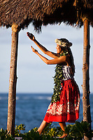 Young Hawaiian woman practicing hula in a beachfront gazebo at sunset