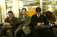 Commuters sleep while others use their i-mode function on their mobile phones during rush hour on trains in Tokyo.