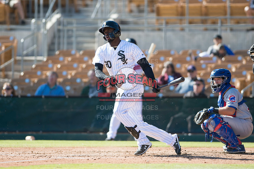 Glendale Desert Dogs center fielder Luis Robert (20), of the Chicago White Sox organization, follows through on his swing in front of catcher P.J. Higgins (12) during an Arizona Fall League game against the Mesa Solar Sox at Camelback Ranch on November 12, 2018 in Glendale, Arizona. Glendale defeated Mesa 4-2. (Zachary Lucy/Four Seam Images)