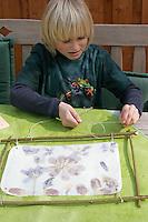 Kinder basteln ein Fensterbild mit Blüten, Junge verknotet Schnur am Holzrahmen des fertigen Fensterbildes als Anbringungsmöglichkeit