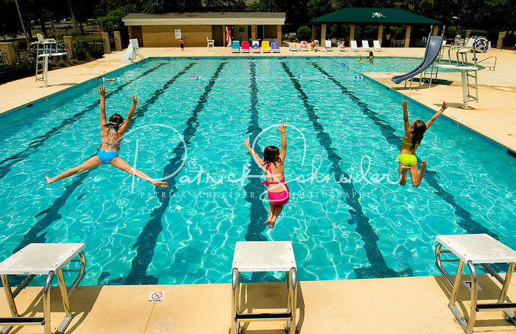 Three young girls jump into a pool at Rolling Hills Country Club in Monroe, NC.