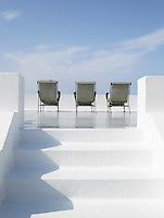 The pristine whilte walls of an elegantly minimal sun terrace at the Hotel Raya Panarea in Italy where three sun-loungers have been set out under idyllic blue skies
