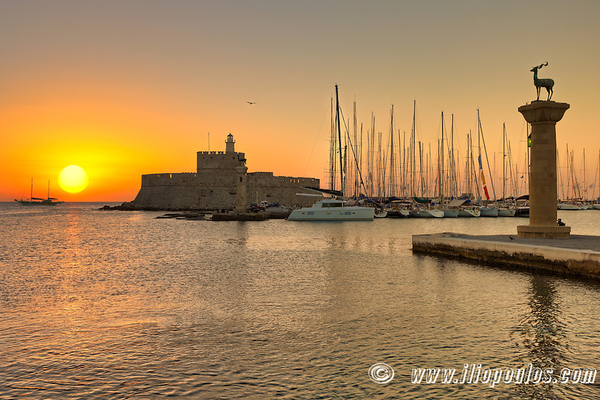 The sunrise at the entrance with the deers of the old port of Rhodes, Greece