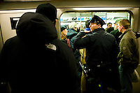 22 January 2006 - New York City, NY - A police officer call for backup after seeing participants in the 5th annual No Pants Subway Ride traveling the #6 line without pants in New York City, USA, 22 January 2006. The artists and pranksters of the Improv' Everywhere group organised the ride, which gathered over 150 participants, in order to surprise and amuse other passengers and themselves. The police issued summons and handcuffed several participants. Photo Credit: David Brabyn.