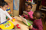 Education Preschool 3-4 year olds pretend play area playing store girl counting papers they are using for money