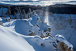 A sun pillar or sun beam at sun rise over the Grand Canyon of the Yellowstone, Yelllowstone National Park, Wyoming, USA. January. Created by reflections off ice crystals hanging in the air.