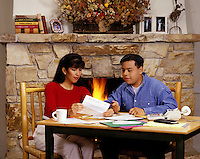 A HISPANIC COUPLE review the monthly bills in front of their FIREPLACE at home