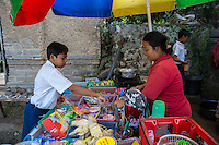 Bali, Indonesia.   Schoolboy Buying Refreshments at a Refreshment Stand Outside his School.  Tenganan Village.