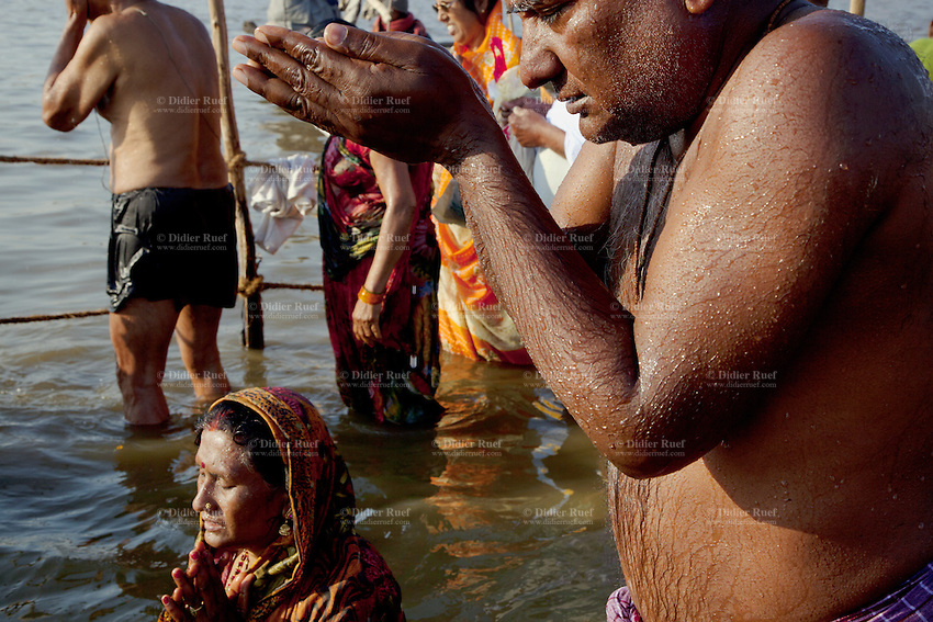 India. Uttar Pradesh state. Allahabad. Maha Kumbh Mela. An Indian Hindu devotee couple takes a holy dip in Sangam. The woman wearing a saree is on her knees in the water and her husband prays. The Kumbh Mela, believed to be the largest religious gathering is held every 12 years on the banks of the 'Sangam'- the confluence of the holy rivers Ganga, Yamuna and the mythical Saraswati. In 2013, it is estimated that nearly 80 million devotees took a bath in the water of the holy river Ganges. The belief is that bathing and taking a holy dip will wash and free one from all the past sins, get salvation and paves the way for Moksha (meaning liberation from the cycle of Life, Death and Rebirth). Bathing in the holy waters of Ganga is believed to be most auspicious at the time of Kumbh Mela, because the water is charged with positive healing effects and enhanced with electromagnetic radiations of the Sun, Moon and Jupiter. The Maha (great) Kumbh Mela, which comes after 12 Purna Kumbh Mela, or 144 years, is always held at Allahabad. Uttar Pradesh (abbreviated U.P.) is a state located in northern India. 8.02.13 © 2013 Didier Ruef