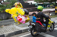 Yogyakarta, Java, Indonesia.  Road Safety.   Little Girl Going Home with her Balloons, no Helmet.