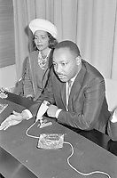 Description Martin Luther King while speaking; next to him his wife Coretta Scott King,<br /> October 20, 1965,<br /> at Schiphol airport, HOLLAND,<br />  before receiving an honorary doctorate in social sciences from the VU University in Amsterdam<br /> <br /> Photographer Fotograaf Onbekend / Anefo