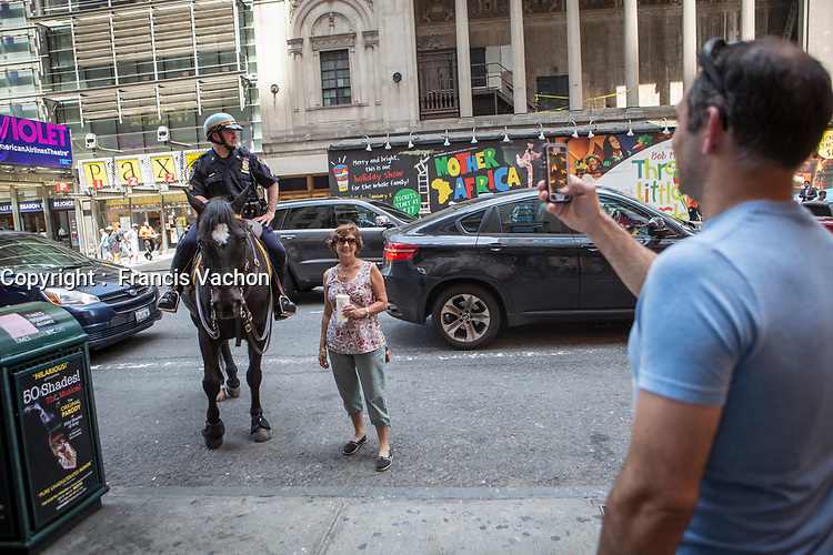 A woman have her picture taken by a NYPD mounted unit in the New York City borough of Manhattan, NY, Monday May 12, 2014.