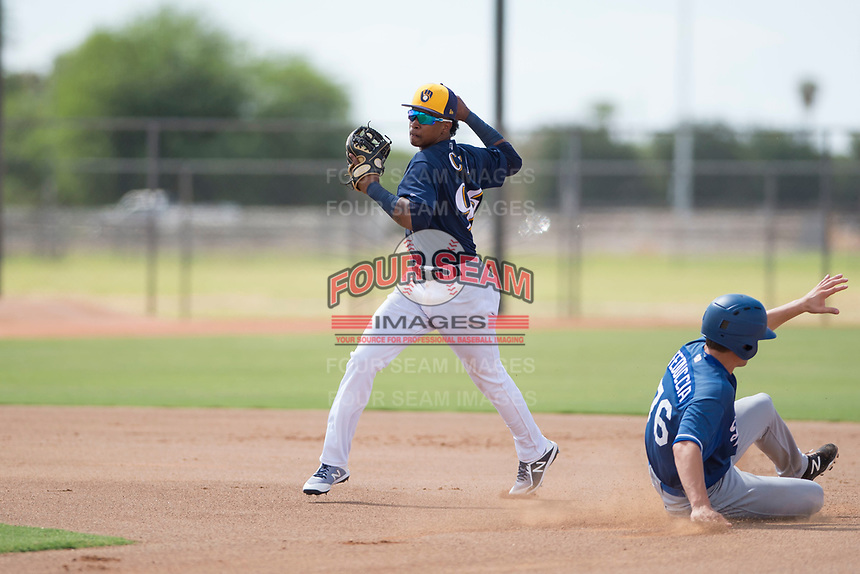 Milwaukee Brewers second baseman Yeison Coca (96) throws to first base on a double play attempt as Hunter Feduccia (76) slides into second base during an Instructional League game against the Los Angeles Dodgers at Maryvale Baseball Park on September 24, 2018 in Phoenix, Arizona. (Zachary Lucy/Four Seam Images)