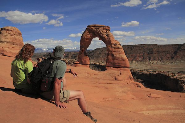 Couple at Delicate Arch in Arches National Park, Moab, Utah, USA. .  John offers private photo tours in Arches National Park and throughout Utah and Colorado. Year-round.