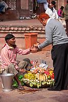 Fatehpur Sikri, Uttar Pradesh, India.  Man Buying Dish of Fruit from Vendor in front of Entrance to Jama Masjid (Dargah Mosque).