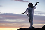 Woman practicing Tai Chi outdoors, dark silhouette in white uniform over sunset skies Image © MaximImages, License at https://www.maximimages.com