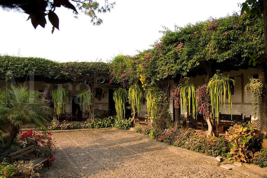 Beautiful courtyard at sunset with flowers at La Posada de Don Rodrigo restaurant in Antigua Guatemal