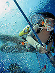 Orchid Island, Taiwan -- A female diver on the anchor line during a deco stop while ascending from the 30+ meter deep Ba Dai ship wreck.