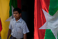 A customer looks at a new design for the Burmese flag on sale in Rangoon (Yangon). The Burmese government have recently introduced a new Burmese flag as part of the 2010 election process.