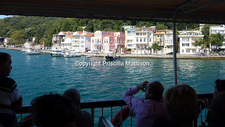 Turkey - September 24, 2009:  Passengers on a boat survey the buildings on the banks of the Bosphorus.