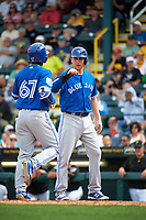 Toronto Blue Jays Andy Burns (1) congratulates Roemon Fields (67) after hitting a home run during a Spring Training game against the Pittsburgh Pirates on March 3, 2016 at McKechnie Field in Bradenton, Florida.  Toronto defeated Pittsburgh 10-8.  (Mike Janes/Four Seam Images)