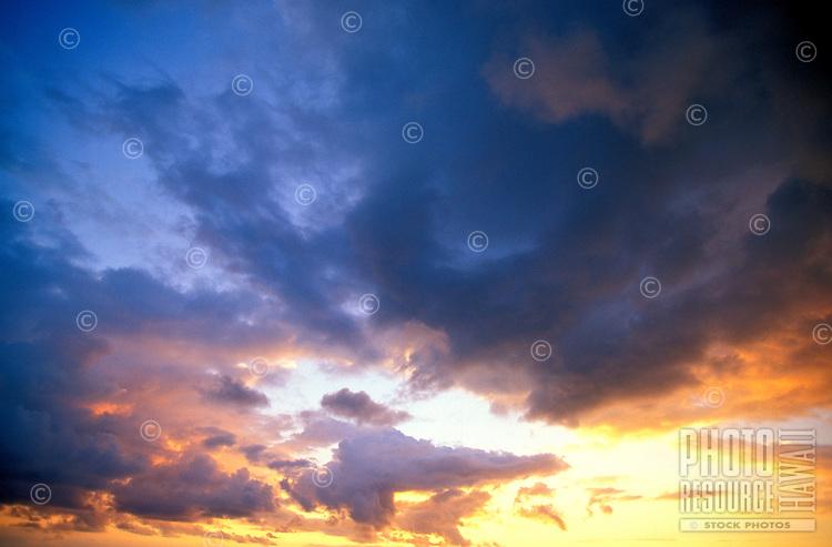 Beautiful dark blue clouds as the sun is setting in Hawaii.