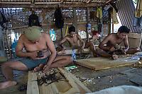 Bali, Indonesia.  Woodcarvers Carving Designs in Windows and Doors in Workshop.