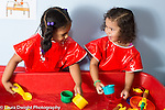 Education Preschool 4 year olds two girls playing with water at water table, talking, friends
