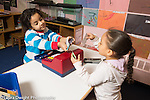 Preschool 3-4 year olds boy and girl playing store play money or credit card  handed to the customer, talking