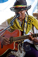 A local female guitarist and singer performs at the King Kamehameha Market in downtown Hilo, Big Island of Hawai'i.