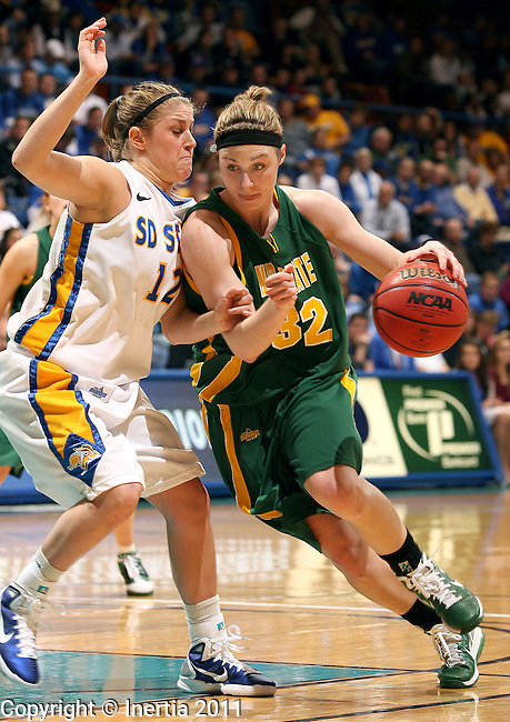 SIOUX FALLS, SD - MARCH 6: Abby Plucker #32 of NDSU drives against the defense of Tara Heiser #12 from SDSU in the second half of their quarter-final game Sunday at the 2011 Summit League Basketball Championships in Sioux Falls, S.D. (Photo by Dave Eggen/Inertia)
