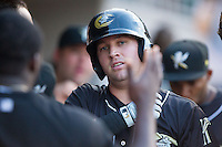 Andy Wilkins (17) of the Charlotte Knights is congratulated by teammates after hitting a home run against the Scranton/Wilkes-Barre RailRiders at BB&T Ballpark on July 17, 2014 in Charlotte, North Carolina.  The Knights defeated the RailRiders 9-5.  (Brian Westerholt/Four Seam Images)