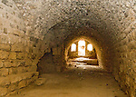 Sunlight streams through empty door and windows into a partially underground barracks chamber at Karak Castle, in Jordan.  Karak was built on a high promontory that was considered nearly impregnable as a border fort at the edge of the Kingdom of Jerusalem.  © Rick Collier