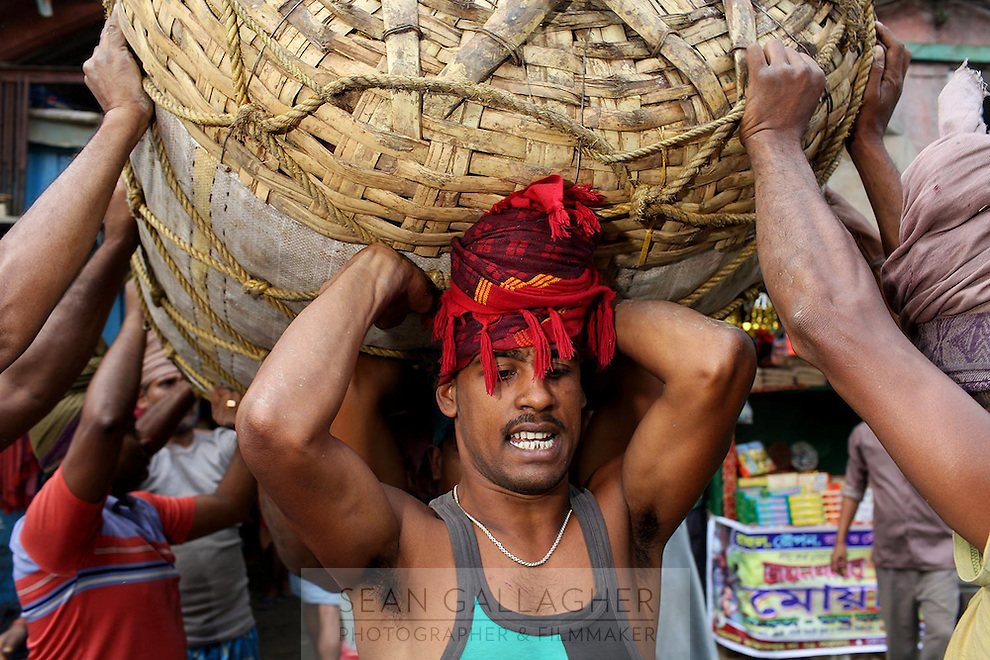 Men carrying large baskets on their heads in the Kolay market in central Kolkata.<br /> <br /> To license this image, please contact the National Geographic Creative Collection:<br /> <br /> Image ID: 1925826 <br />  <br /> Email: natgeocreative@ngs.org<br /> <br /> Telephone: 202 857 7537 / Toll Free 800 434 2244<br /> <br /> National Geographic Creative<br /> 1145 17th St NW, Washington DC 20036