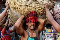 Men carrying large baskets on their heads in the Kolay market in central Kolkata.<br />