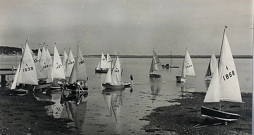 It's some time around 1960, and with the tide flooding gently into Sutton Creek, the Heron Class are getting ready to race at Kilbarrack Sailing Club, while beyond a Snipe crew are preparing to board their newly-floating boat on her drying mooring