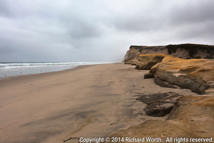 Heavy overcast looms over the bluffs at Pomonio State Beach south of Half Moon Bay on the California Coast.