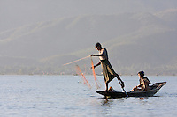 Myanmar, Burma.  Man and Wife Fishing late in the Day.  Inle Lake, Shan State.  The man is rowing with one leg in the style common to Inle Lake.
